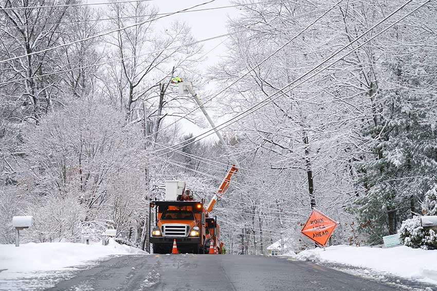 Worker repairing electrical line after winter snow storm
