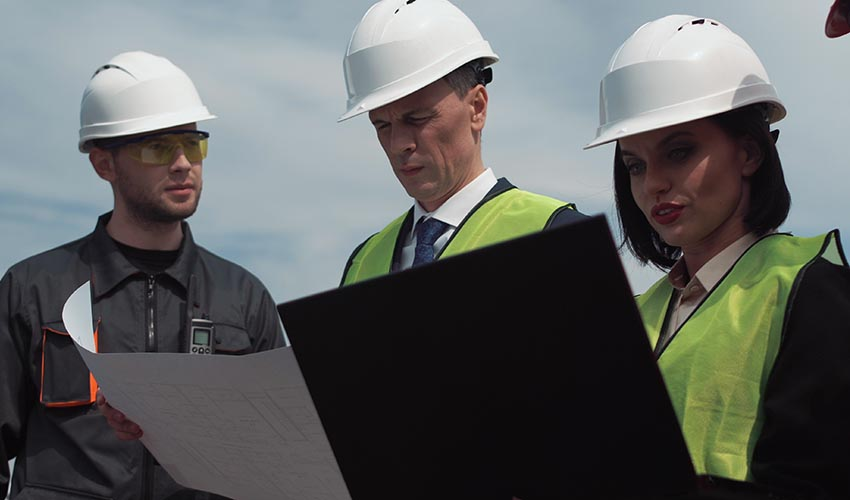 Two men and a women wearing hardhats reviewing blueprints.