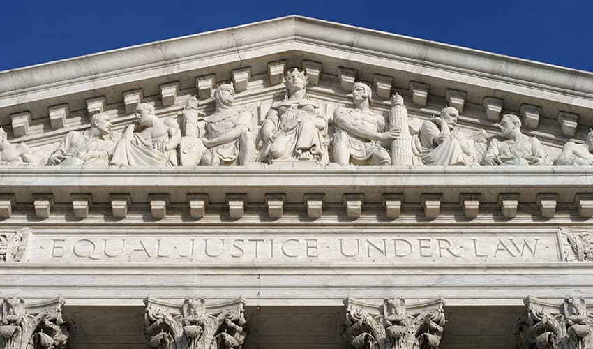 """Closeup of the pediment of a building with the words """"Equal Justice Under Law"""" etched in relief"""
